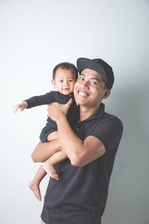 carry on: A portrait of a Young Asian father holding his adorable baby on white background