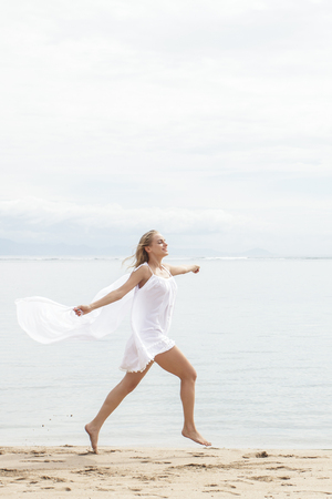 scarf beach: portrait of young woman running with with scarf and feeling free on the beach