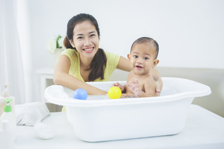 portrait of a baby having a bath by his mother using tub at home