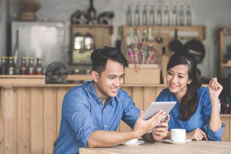カフェで一緒にタブレットを使用して 2 つの若いビジネス パートナーの肖像画 写真素材