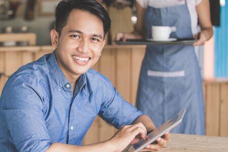 Imagen de hombre joven feliz que usa la tableta digital en el café Foto de archivo - 61894040