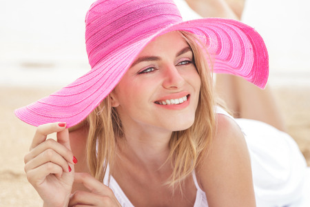 a close up: close up portrait of Relaxing woman wearing pink sunhat on beach vacation lying on sand Stock Photo