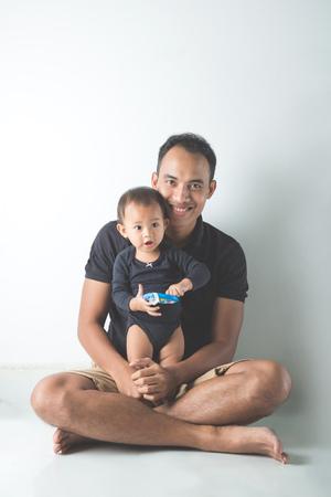 若いアジアの肖像画は、白い背景の彼の愛らしい赤ん坊を保持父します。 写真素材