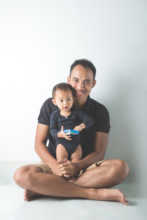 Un ritratto di un giovane padre asiatico che tiene il suo bambino adorabile su sfondo bianco Archivio Fotografico - 58428556