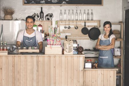 2 persons only: portrait of two young cafe staff at work standing and smiling to camera