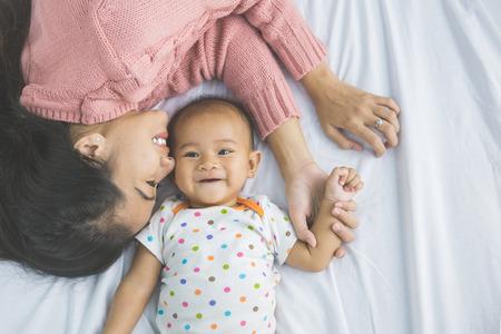 Un retrato de una joven madre con su bebé en la cama Foto de archivo - 58466680