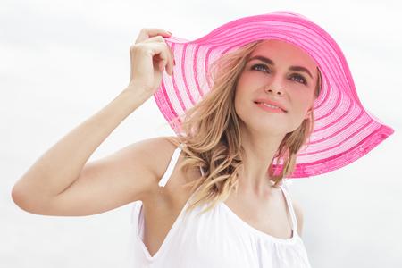 sunhat: portrait of beautiful woman wearing pink sunhat on the beach enjoying summer