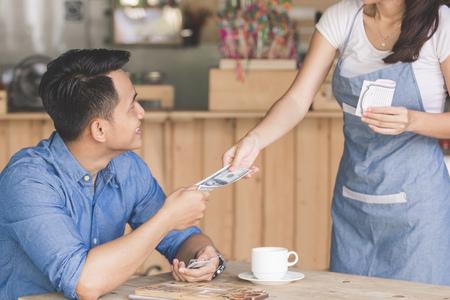 pagando: Sonriendo cliente paga en efectivo en la cafetería