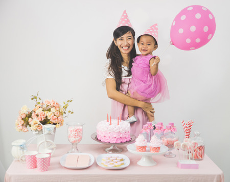 portrait of happy asian baby girl celebrating her first birthday with mother at home