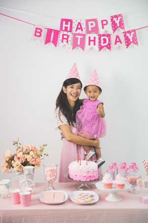 sugarpaste: portrait of happy asian baby girl celebrating her first birthday with mother at home