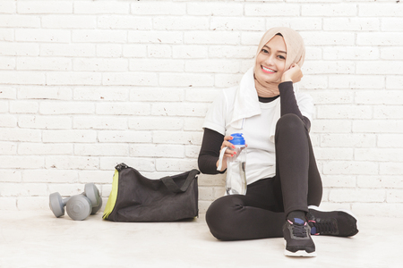 portait of asian sporty woman sitting on the floor resting after workout with white brick wall on the background