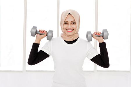 portrait of beautiful asian sporty woman lifting dumbbells