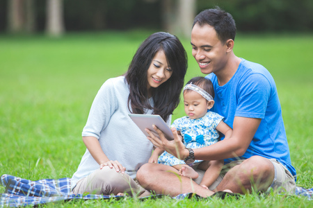 Baby in the park using tablet pc. modern happy family Stock Photo