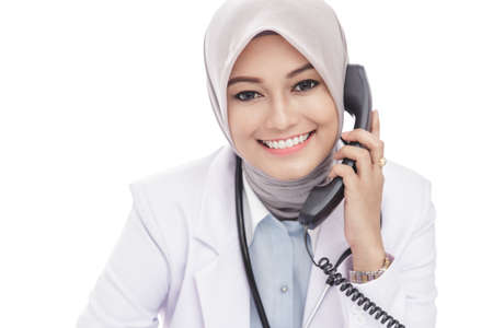 asian nurse: close up portrait of beautiful asian female doctor talking on the phone while smiling isolated on white background
