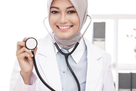 close up portrait of asian female doctor smiling while using stethoscope Stock Photo