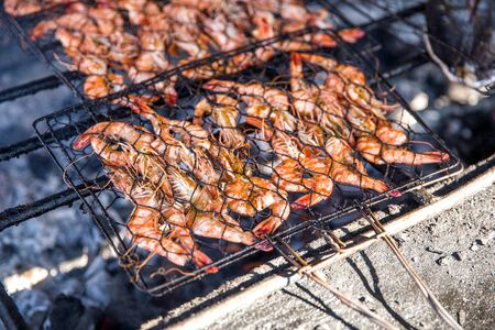 close up of Grilling shrimp on campfire with charcoal