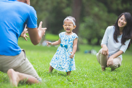 baby in hands: Cute funny happy baby making his first steps on a green grass, mother holding her hands supporting by learning to walk Stock Photo