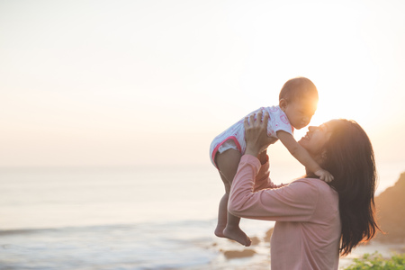 happy mom: Portrait of mother and baby playing and smiling under summer sunset