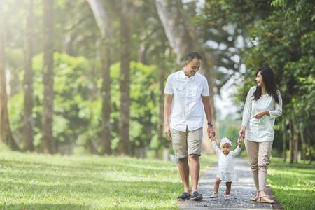 父、母と自分の赤ちゃんの肖像画が一緒に公園を歩く