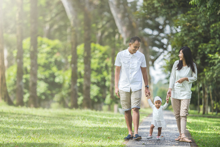 portrait of father, mother and their  baby walk along the park together Banco de Imagens
