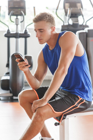 take a break: portrait of young man playing mobilephone while take a break during workout at the gym Stock Photo