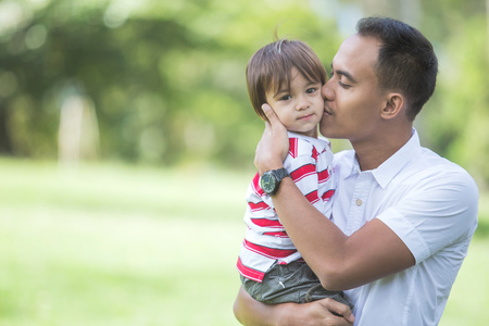 asian lifestyle: portrait of Father with his baby boy in park Stock Photo