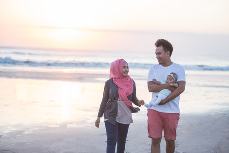 muslim baby: happy family enjoying summer holiday together in the beach