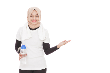 presenting: portrait of muslim sporty woman holding a bottle of mineral water while presenting copy space isolated on white background Stock Photo