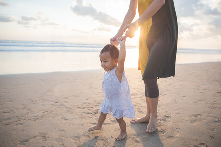 warm water: portrait of a mother is teaching her daughter walks on the beach