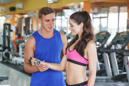 young guy: portrait of sporty woman exercising with her instructor at the gym
