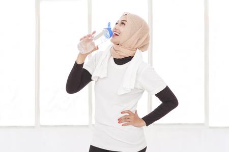 tomando agua: Retrato de mujer asiática deportiva beber agua mineral después del entrenamiento