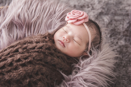 comfy: close up portrait of cute little baby girl sleeping comfy on fur blanket