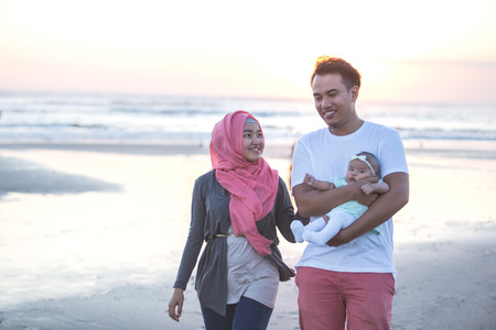 islam: happy family enjoying summer holiday together in the beach