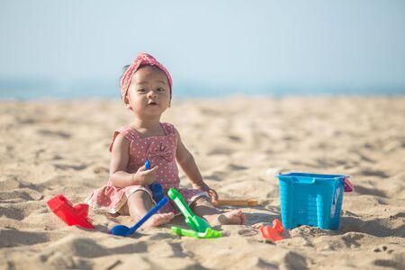 Cute niña jugando con los juguetes de playa en playa tropical Foto de archivo