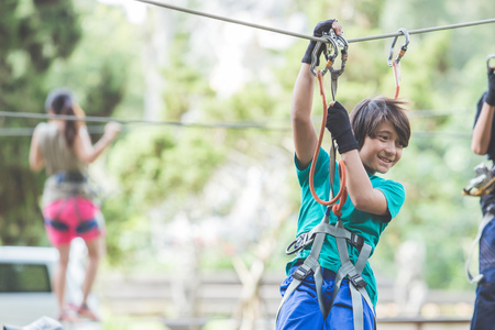 outbound: portrait of active brave boy enjoying outbound climbing at adventure park on tree top