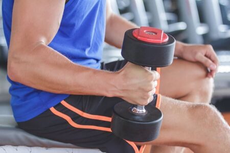 sports training: close up portrait of strong arm holding and lifting dumbbell at the gym Stock Photo