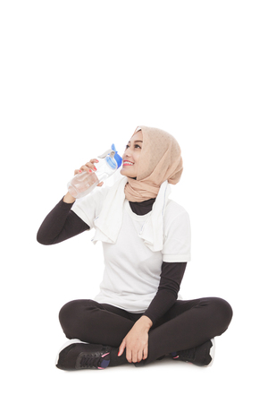 portrait of young asian woman drinking mineral water during break after workout isolated on white background