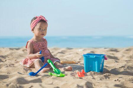 Cute niña jugando con los juguetes de playa en playa tropical