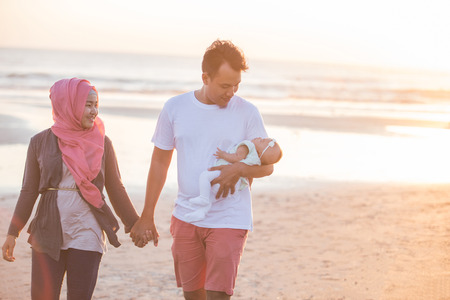 petite fille musulmane: portrait of happy parent with newborn baby at the beach having fun together Banque d'images