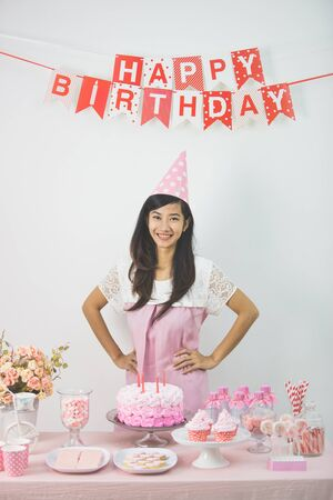 sugarpaste: portrait of happy asian girl celebrating her birthday party standing with cake and cookies in front of her Stock Photo