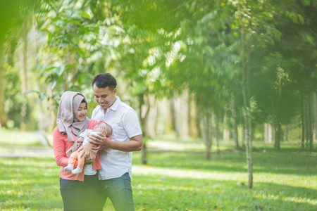 muslim baby girl: portrait of Beauty Mother and father with their newborn baby in the park