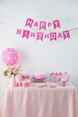 Retrato de la cadena de bandera de la bandera del feliz cumpleaños y una mesa con lleno de dulces y pastel Foto de archivo - 62207153