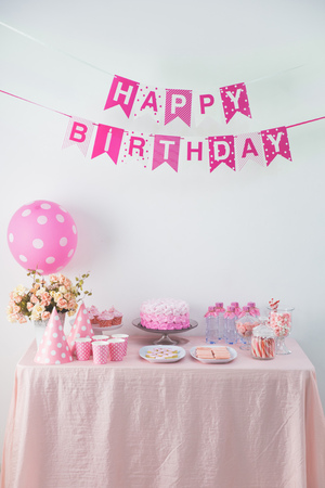 Ritratto di felice compleanno bandiera catena banner e un tavolo con il pieno di caramelle dolce e torta Archivio Fotografico - 62207153