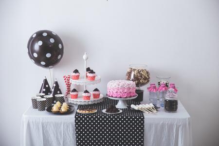 portrait de la décoration de fête d'anniversaire en noir et blanc avec plein de gâteaux et de bonbons sucrés Banque d'images