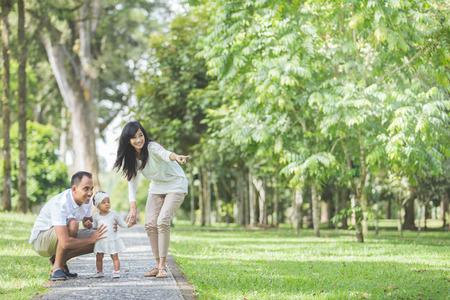 Retrato de una hermosa familia con el bebé lindo en el parque que se divierte junto Foto de archivo