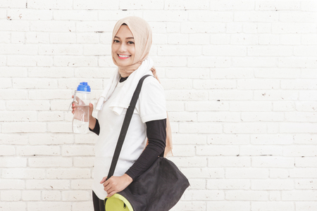 portrait of asian sporty woman carrying sports bag anf a bottle of water with copy space on white brick wall for background