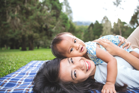 portrait of Beauty Mother and her Child playing in Park together Stock Photo