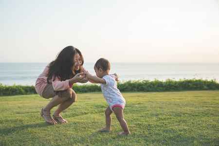Cute funny happy baby making his first steps on a green grass, mother holding her hands supporting by learning to walk Stockfoto