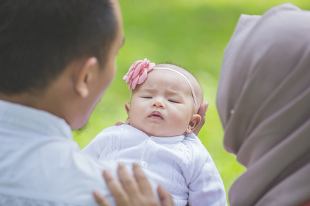 mother baby: portrait of happy Father and mother with their newborn baby in park Stock Photo