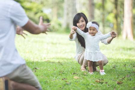 portrait of Beautiful baby learn to walk with their parent in the park Stock Photo